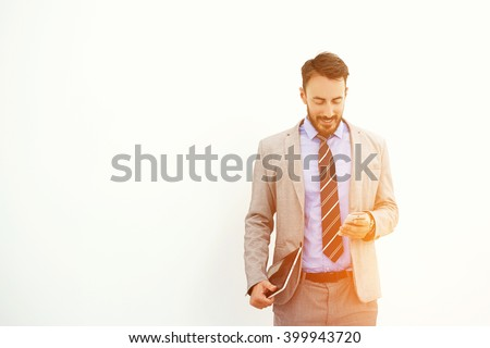 Man professional trader with digital tablet in hand is reading good news on mobile phone from his client about purchase of securities, while is standing near copy space for your advertising content - stock photo