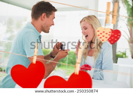 Man proposing marriage to his shocked blonde girlfriend against hearts hanging on the line - stock photo
