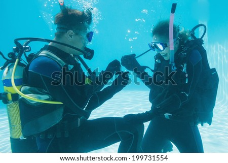 Man proposing marriage to his shocked girlfriend underwater in scuba gear on their holidays - stock photo
