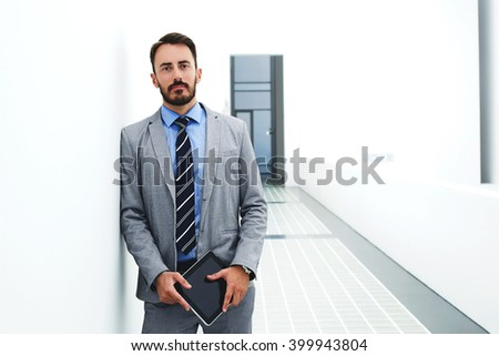 Man prosperous entrepreneur is holding touch pad and looking at camera, while is resting after meeting with partners. Male skilled boss with digital tablet in hands is standing in corridor company - stock photo
