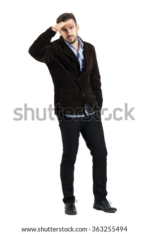 Man protecting eyes from bright sunshine with hand on his forehead in warm clothes. Full body length portrait isolated over white studio background.  - stock photo