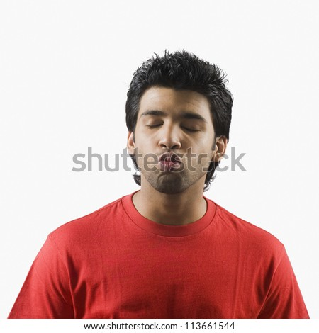 Man puckering with his eyes closed - stock photo