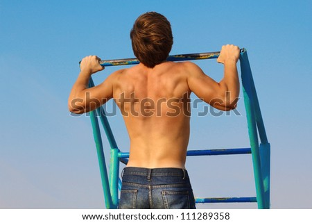 Man pull-ups on a bar over blue sky. From the back.