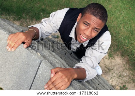 Man pulling himself up a wall