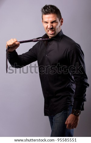 man pulling his tie looking aggressive - stock photo