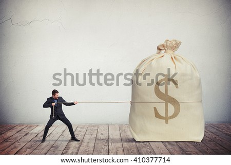 Man pulling on a rope big bag of money, grey wall on background