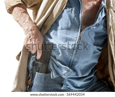 Man pulls a gun out of his pocket isolated on white background - stock photo