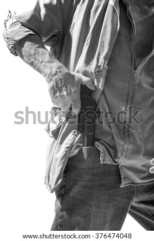 Man pulls a gun out of his pocket isolated on white background, black and white photo - stock photo