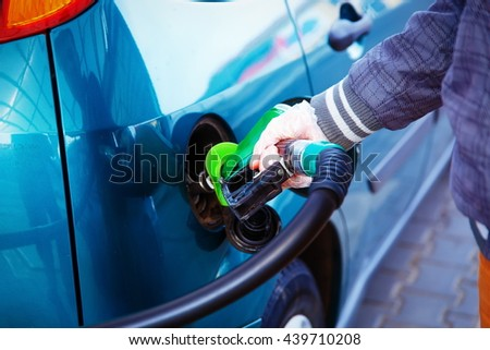 man pumping gasoline fuel in car at gas station. transportation concept