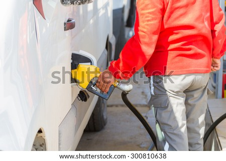 Man pumping gasoline fuel in car at petrol station