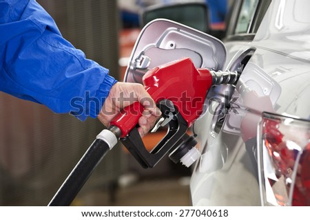 Man Pumping Gasoline Into Silver Car With Red Gasoline Nozzle - stock photo