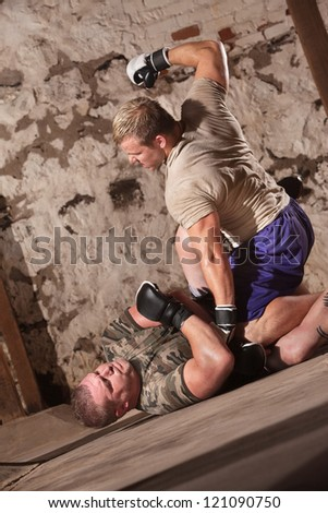 Man punching pinned opponent on the ground - stock photo