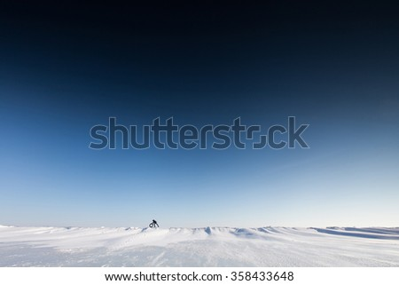 Man pushes a wheel on a snowy surface. After a snowfall - stock photo