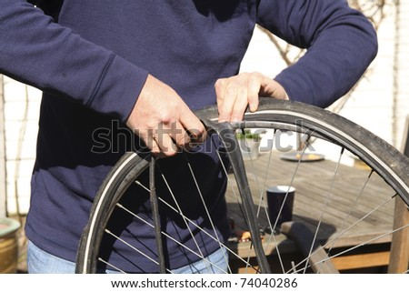 Man pushes repaired rubber tire inside outer tire - stock photo