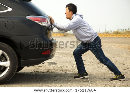 Man pushing a broken car down the rock road  - stock photo