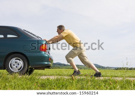 Man pushing a car with empty gas tank - stock photo