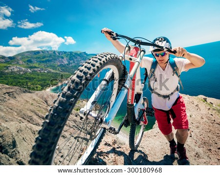 Man pushing a mountain bike up the hill. Adventure travel on bicycle.