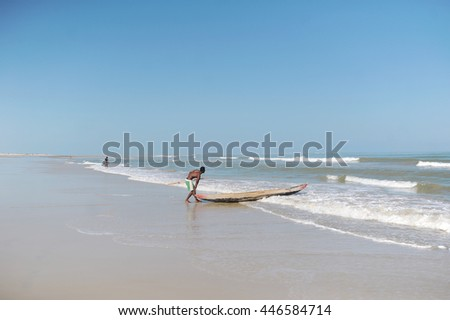 Man pushing a traditional canoe in Madagascar