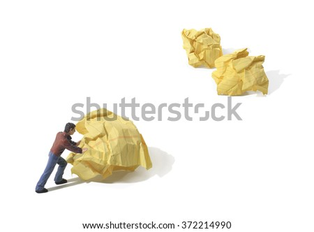 Man pushing crumpled paper wads around