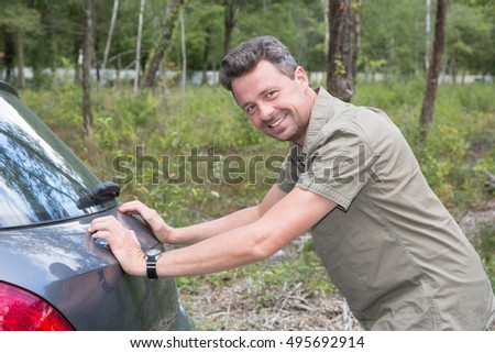 Man pushing his broken car or a car out of gas, on a sunny day