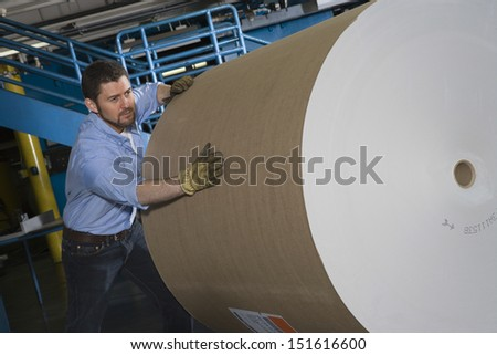 Man pushing huge roll of paper in newspaper factory - stock photo