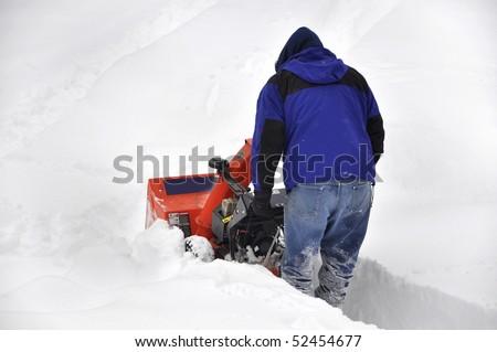man pushing snow blower through deep snow - stock photo