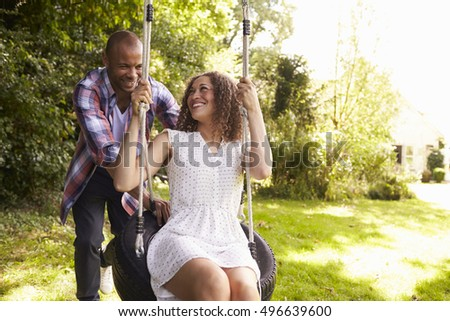 Man Pushing Woman On Tire Swing In Garden