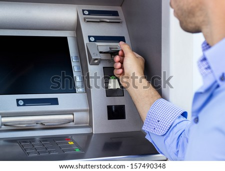 Man put credit card into ATM  - stock photo