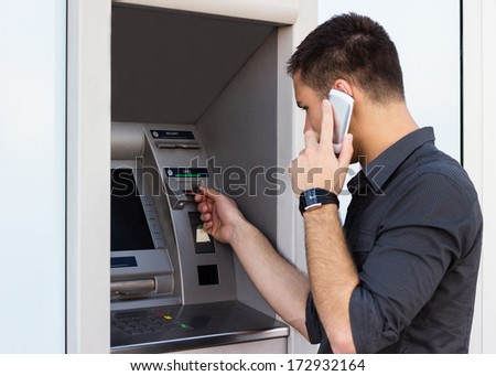 Man put his credit card at the atm  - stock photo