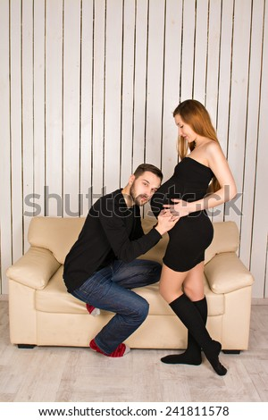 man put his ear to the belly of his pregnant wife and listening to his unborn child - stock photo