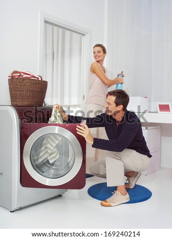 Man puts clothes into the washing machine - stock photo