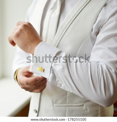 man puts cufflinks on sleeve white shirts - stock photo