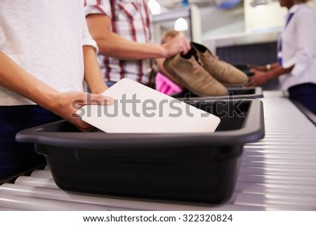 Man Puts Digital Tablet Into Tray For Airport Security Check - stock photo