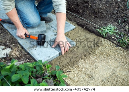 Man puts paving in the garden - stock photo