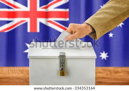 Man putting a ballot into a voting box - Australia - stock photo