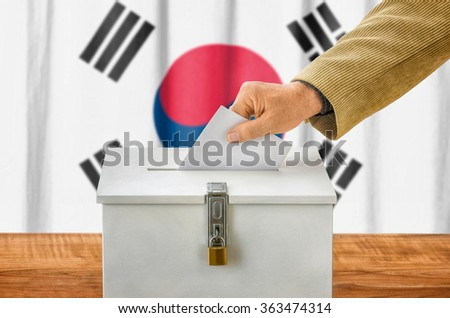 Man putting a ballot into a voting box - South Korea - stock photo