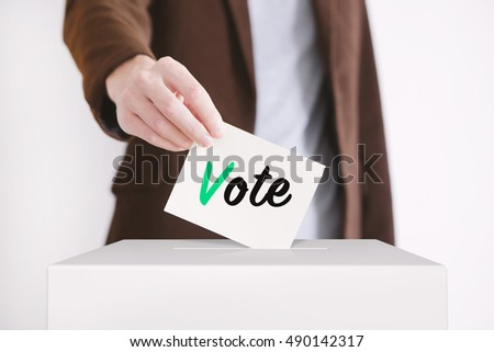 Man putting a ballot into a voting box. Toned image.