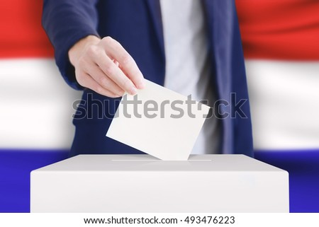 Man putting a ballot into a voting box with Holland flag on background.