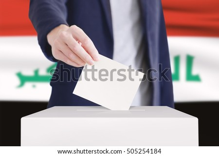 Man putting a ballot into a voting box with Iraq flag on background.