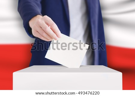 Man putting a ballot into a voting box with Polish flag on background.