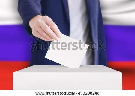 Man putting a ballot into a voting box with Russian flag on background.