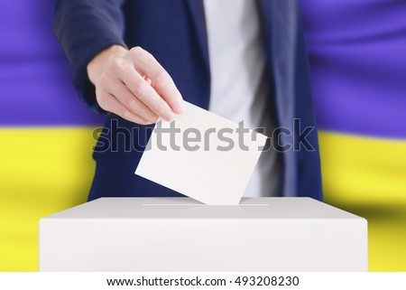 Man putting a ballot into a voting box with Ukrainian flag on background.
