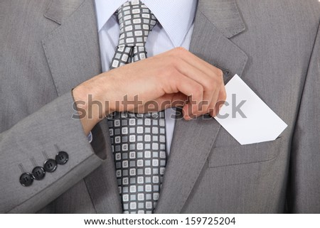 Man putting a business card into his pocket - stock photo