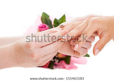 Man putting a golden ring on woman's hand, isolated background