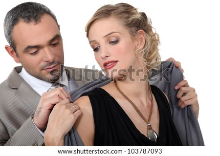Man putting a shawl around his date's shoulders