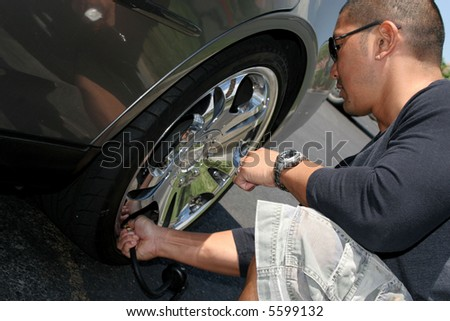 Man Putting Air into a Tire