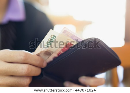 Man putting banknotes in his wallet.