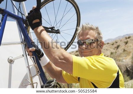 Man putting bicycle onto car rack, portrait