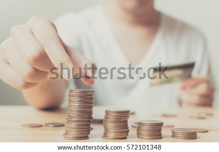 Man putting coins on stack with holding credit card, Concept business, finance, money saving