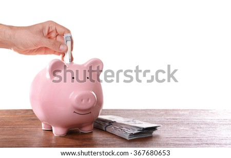 Man putting dollar banknotes in pig moneybox